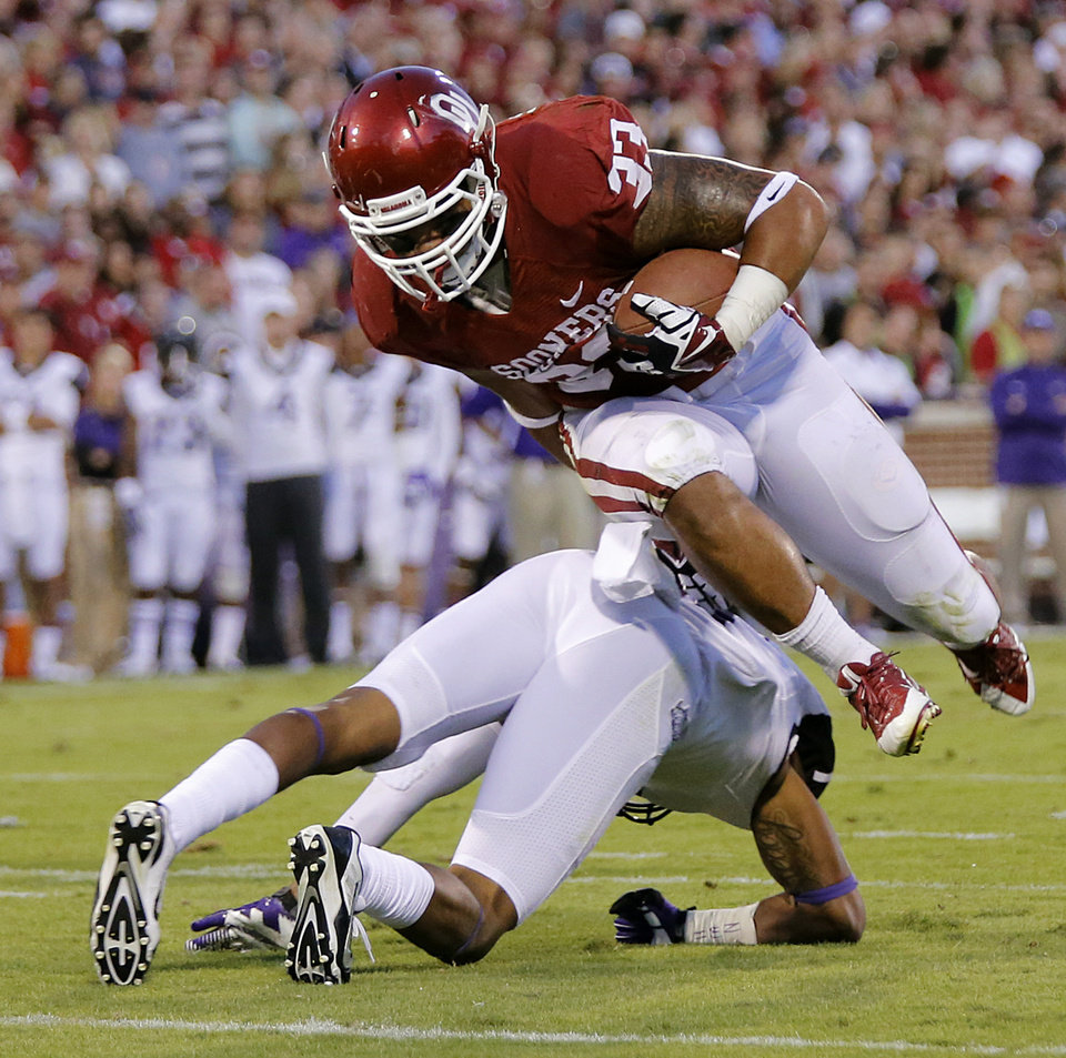 Oklahoma's Trey Millard (33) leaps over a TCU defender during the college football game between the University of Oklahoma Sooners (OU) and the Texas Christian University Horned Frogs (TCU) at the Gaylord Family-Oklahoma Memorial Stadium on Saturday, Oct. 5, 2013 in Norman, Okla.   Photo by Chris Landsberger, The Oklahoman
