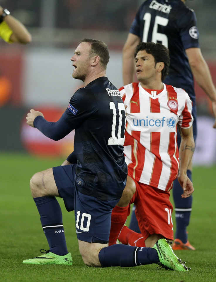 Photo - Manchester United's Wayne Rooney reacts to the referee's decision as Nelson Valdez looks on during their Champions League, round of 16, first leg soccer match at Georgios Karaiskakis stadium, in Piraeus port, near Athens, on Tuesday, Feb. 25, 2014. Olympiakos won 2-0. (AP Photo/Thanassis Stavrakis)