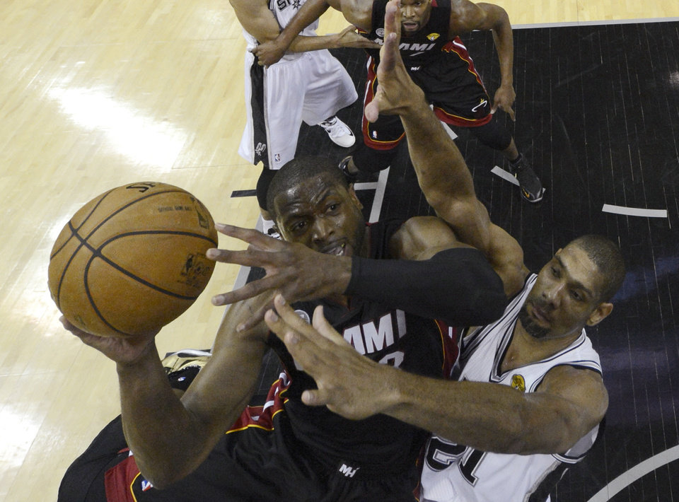 Miami Heat's Dwyane Wade (3) is defended by San Antonio Spurs' Tim Duncan, during the first half at Game 4 of the NBA Finals basketball series, Thursday, June 13, 2013, in San Antonio. (AP Photo/Derick E. Hingle, Pool)