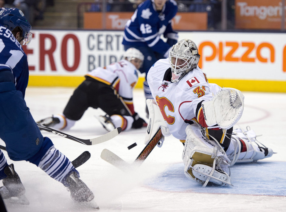 Photo - Calgary Flames goaltender Karri Ramo makes a save on Toronto Maple Leafs right winger Phil Kessel during second period NHL action in Toronto on Tuesday April 1, 2014.  (AP Photo/The Canadian Press, Frank Gunn)