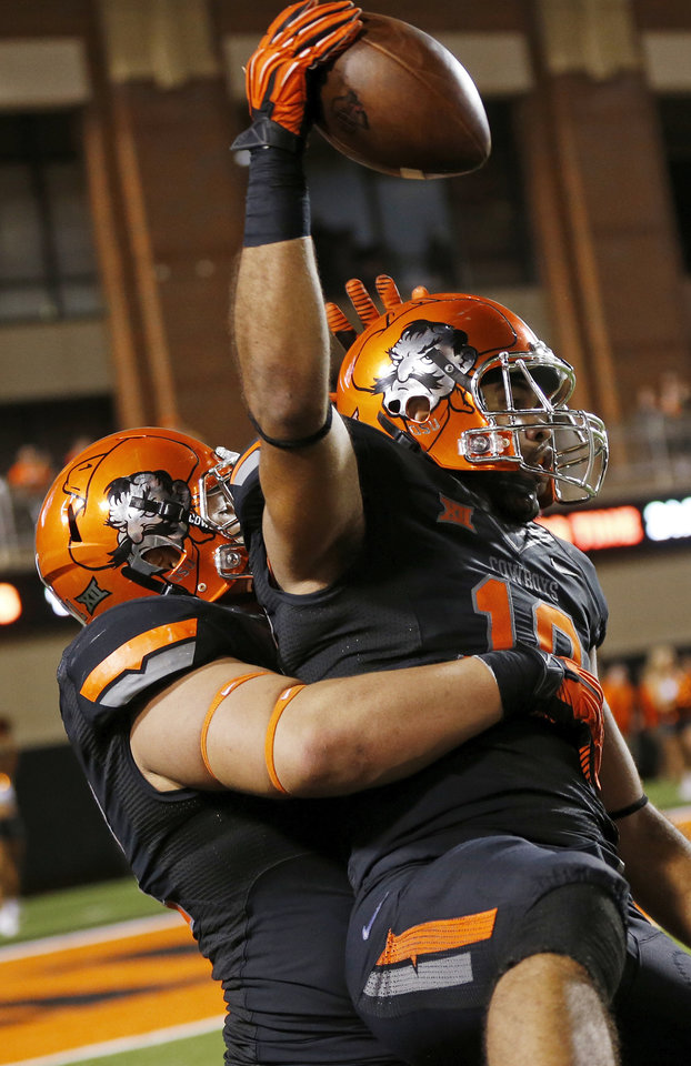 Photo - Oklahoma State's James Castleman (91) lifts up Oklahoma State's Seth Jacobs (10) as they celebrate an interception by Jacobs in the fourth quarter during a college football game between the Oklahoma State Cowboys (OSU) and the Texas Tech Red Raiders at Boone Pickens Stadium in Stillwater, Okla., Thursday, Sept. 25, 2014. OSU won, 45-35. Photo by Nate Billings, The Oklahoman