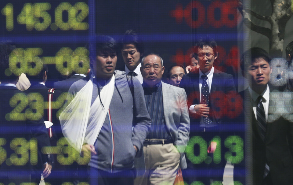 Photo - People are reflected on the electronic board of a securities firm in Tokyo, Friday, April 11, 2014. Tokyo's Nikkei 225 stock average fell more than 400 points at one point in morning trading. (AP Photo/Koji Sasahara)
