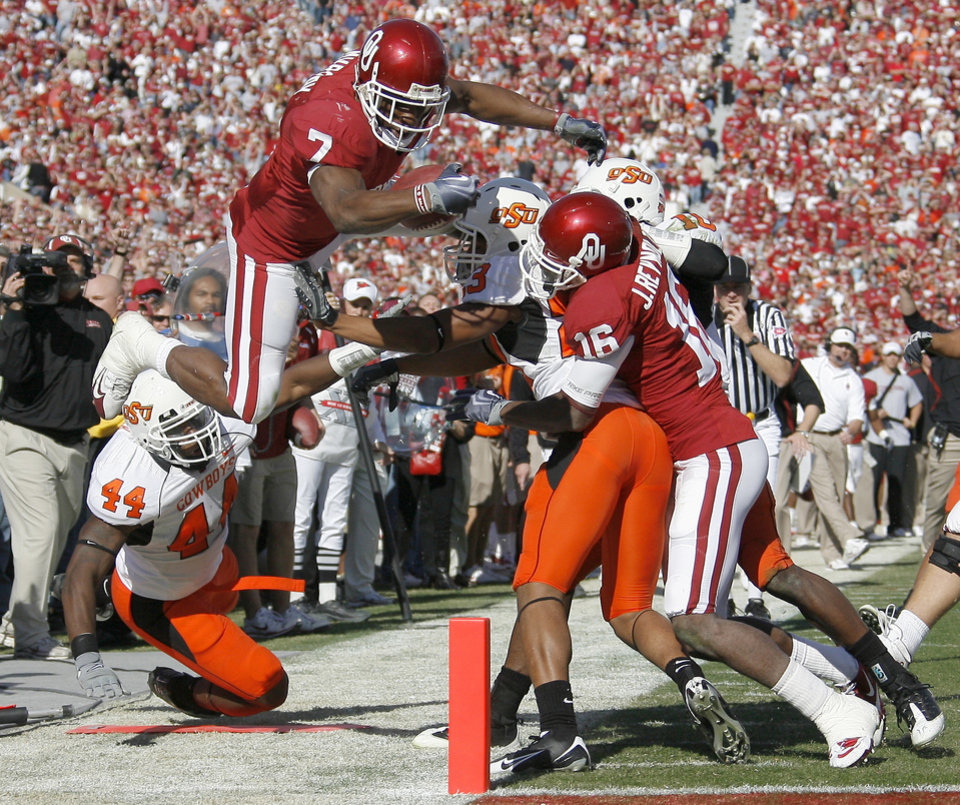 Photo - OU's DeMarco Murray scores a touchdown in front of OSU's Donald Booker, at left, Terrance Anderson and Markelle Martin and OU's Jaz Reynolds during the first half of the Bedlam college football game between the University of Oklahoma Sooners (OU) and the Oklahoma State University Cowboys (OSU) at the Gaylord Family-Oklahoma Memorial Stadium on Saturday, Nov. 28, 2009, in Norman, Okla.