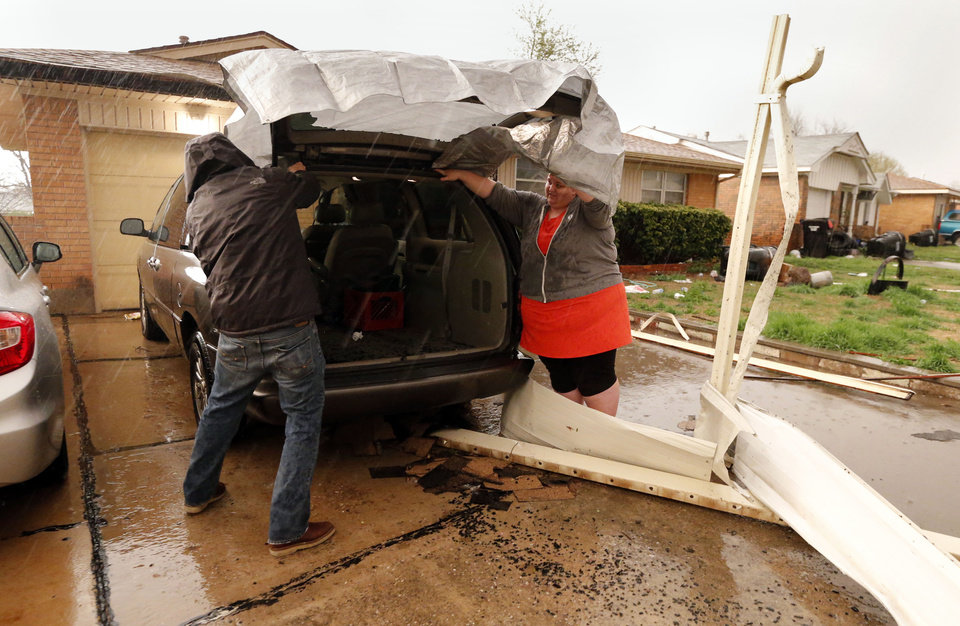 Photo - Residents scramble to cover broken glass near SE 4th and Irving after tornado force winds on Wednesday, March 25, 2015 in Moore, Okla. Photo by Steve Sisney, The Oklahoman