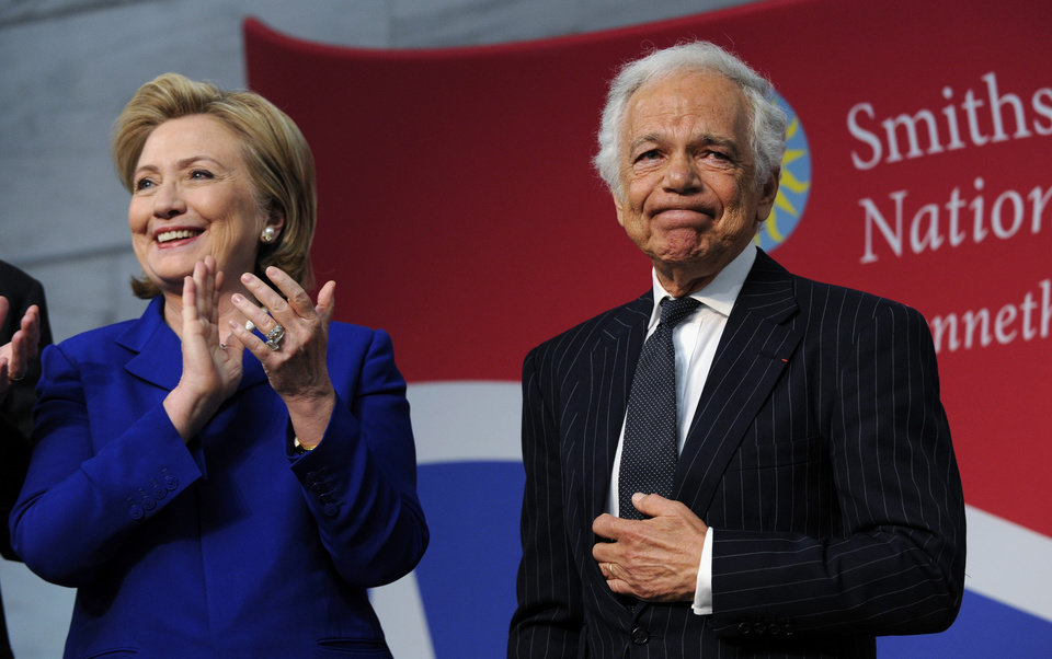 "Photo - Designer Ralph Lauren is applauded by former Secretary of State Hillary Clinton after Lauren receiving the James Smithson Bicentennial Medal ""for his embodiment of the American experience through the medium of fashion, design and philanthropy"