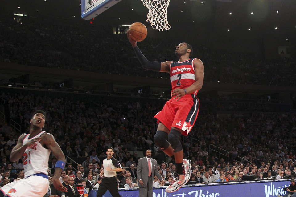 Photo - Washington Wizards' John Wall (2) scores as New York Knicks' Iman Shumpert looks on during the first half of an NBA basketball game, Tuesday, April 9, 2013, at Madison Square Garden in New York.  (AP Photo/Mary Altaffer)