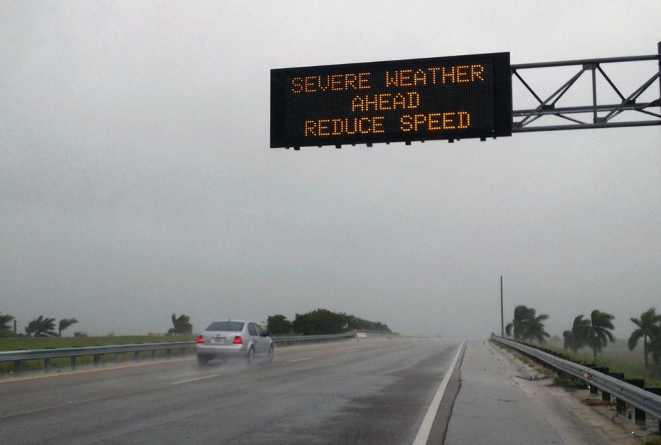 Photo - A message warns drivers of severe weather on Sunday, Aug. 26, 2012, in Miami. Isaac gained fresh muscle Sunday as it bore down on the Florida Keys, with forecasters warning it could grow into a dangerous Category 2 hurricane as it nears the northern Gulf Coast. (AP Photo/The Miami Herald, Hector Gabino) ORG XMIT: FLMIH102