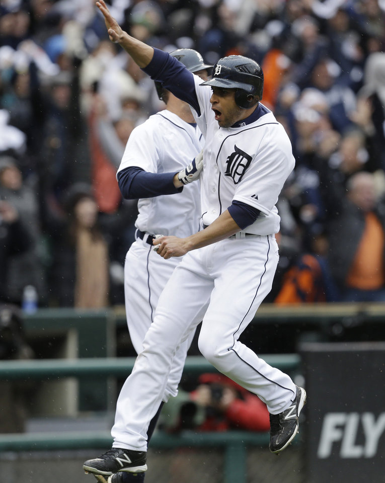 Photo -   Detroit Tigers' Omar Infante high fives a teammate after scoring the game winning run on a sacrifice fly by teammate Don Kelly during the ninth inning of Game 2 of the American League division baseball series against the Oakland Athletics, Sunday, Oct. 7, 2012, in Detroit. (AP Photo/Paul Sancya)