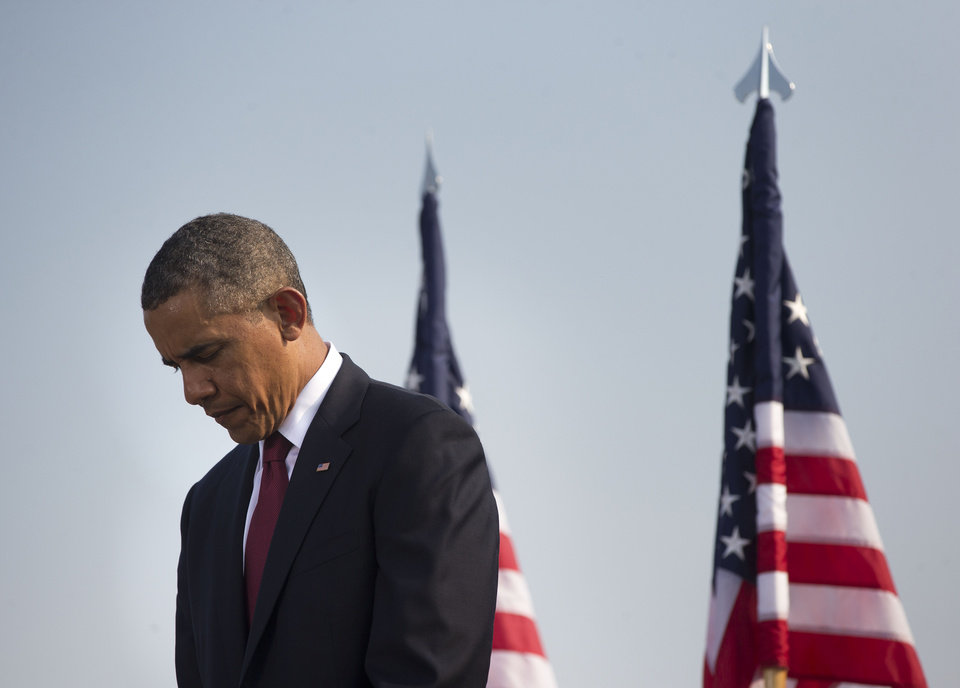 Photo - President Barack Obama lowers his head during a moment of silence at the Pentagon, Wednesday, Sept. 11, 2013, during a ceremony to mark the 12th anniversary of the 9/11 attacks. (AP Photo/Pablo Martinez Monsivais)
