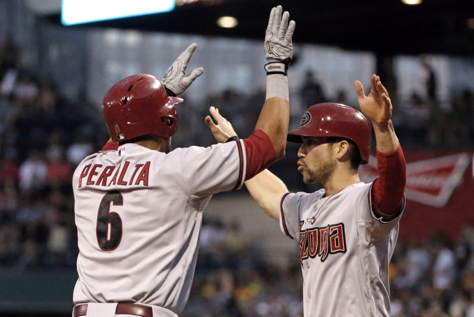 Photo - Arizona Diamondbacks' David Peralta (6) celebrates with teammate Ender Inciarte who was on base for his two-run home run off Pittsburgh Pirates starting pitcher Vance Worley during the sixth inning of a baseball game in Pittsburgh Thursday, July 3, 2014. (AP Photo/Gene J. Puskar)