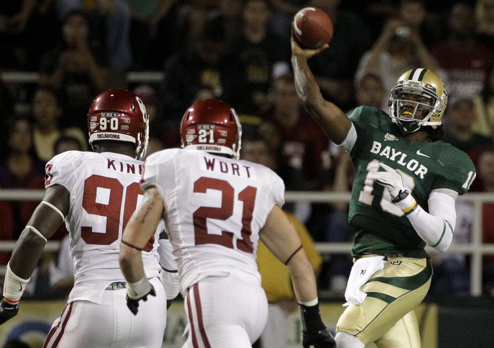 Oklahoma defensive end David King (90) and linebacker Tom Wort (21) give chase as Baylor quarterback Robert Griffin III (10) passes in the first half of an NCAA college football game on Saturday, Nov. 19, 2011, in Waco, Texas. (AP Photo/Tony Gutierrez) ORG XMIT: TXTG209
