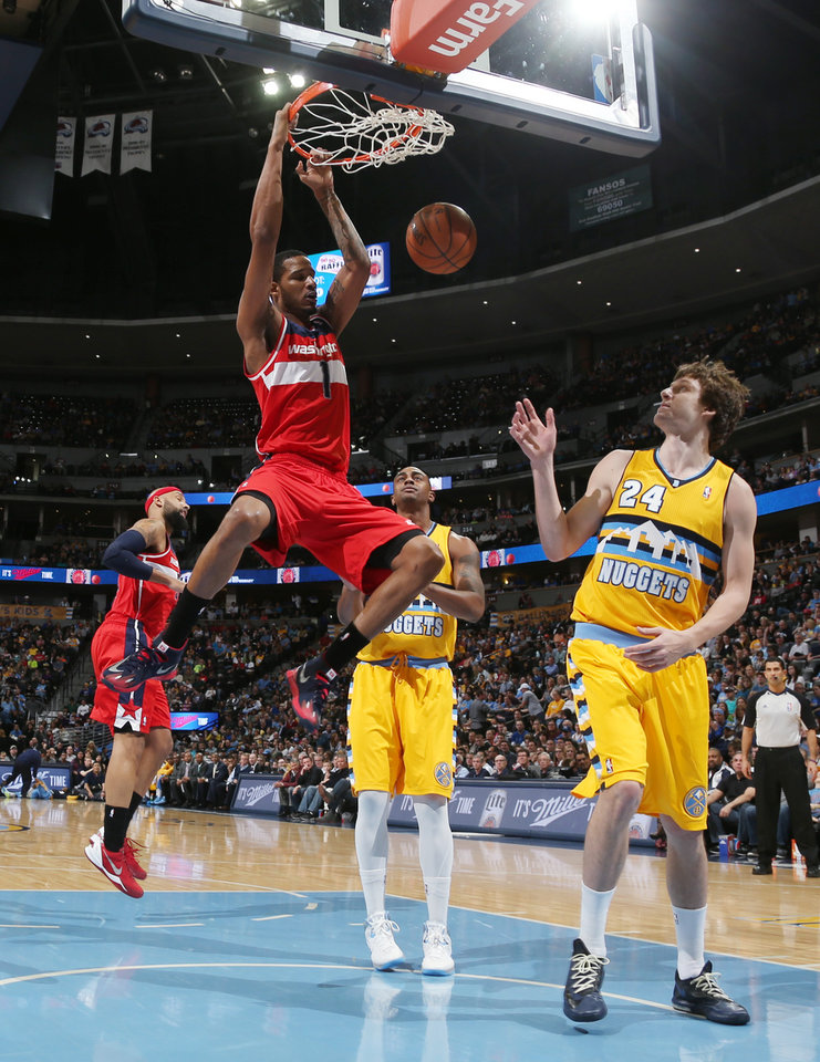 Photo - Washington Wizards forward Trevor Ariza, left, hangs from the rim after dunking as Denver Nuggets forwards Darrell Arthur, center, and Jan Vesely, of the Czech Republic, look on in the first quarter of an NBA basketball game in Denver on Sunday, March 23, 2014. (AP Photo/David Zalubowski)