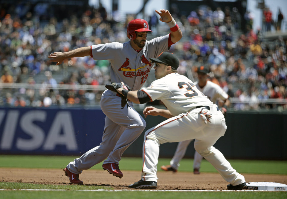 Photo - St. Louis Cardinals' Matt Carpenter, left, makes it safely back to first base on a pick off attempt as San Francisco Giants first baseman Adam Duvall, right, waits for the throw in the first inning of their baseball game Thursday, July 3, 2014, in San Francisco. (AP Photo/Eric Risberg)