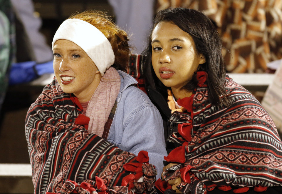 Norman North students Maddie Garrett, 10th, and Tiffany Hurt, 12th, try to stay warm during the high school football game between Norman North and Edmond North in Edmond at Wantland Stadium Friday, Friday, October 18, 2013.  Photo by Doug Hoke, The Oklahoman
