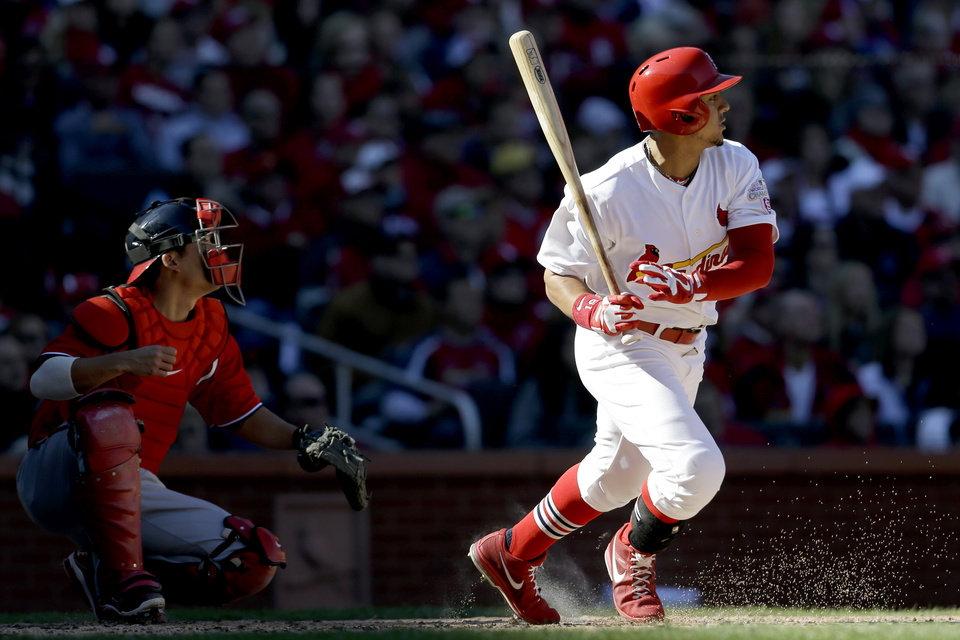 St. Louis Cardinals\' Jon Jay hits a sacrifice fly to score Daniel Descalso as Washington Nationals catcher Kurt Suzuki, left, watches during the second inning in Game 1 of baseball\'s National League division series, Sunday, Oct. 7, 2012, in St. Louis. (AP Photo/Jeff Roberson)