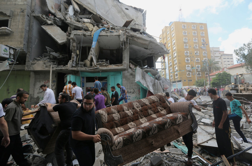 Photo - Palestinians salvage their usable belongings from the rubble of their homes in an apartment building after it was hit by an Israeli missile strike in Gaza City, Friday, July 18, 2014. Israeli troops pushed deeper into Gaza on Friday to destroy rocket launching sites and tunnels, firing volleys of tank shells and clashing with Palestinian fighters in a high-stakes ground offensive meant to weaken the enclave's Hamas rulers. (AP Photo/Hatem Moussa)