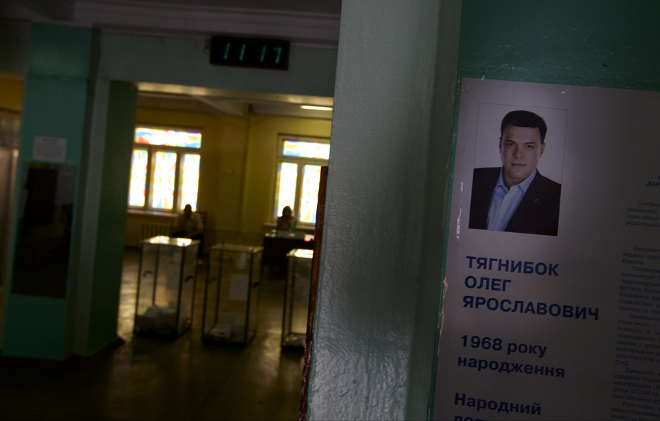 Photo - A portrait of presidential candidate Oleh Tyahnybok, leader of the nationalist Svoboda (Freedom) party, is seen on information stand at a polling station in Mariupol, Ukraine, on Sunday, May 25, 2014. Ukraine's critical presidential election got underway Sunday under the wary scrutiny of a world eager for stability in a country rocked by a deadly uprising in the east. (AP Photo/Ivan Sekretarev)