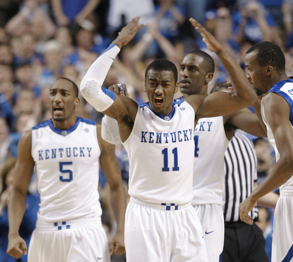 Photo - CELEBRATION: University of Kentucky's John Wall (11) celebrates with teammates from left, Ramon Harris, Patrick Patterson, and Perry Stevenson during the second half of an NCAA college basketball game against Louisville in Lexington, Ky., Saturday, Jan. 2, 2010. Kentucky won 71-62.  (AP Photo/Ed Reinke) ORG XMIT: KYER107