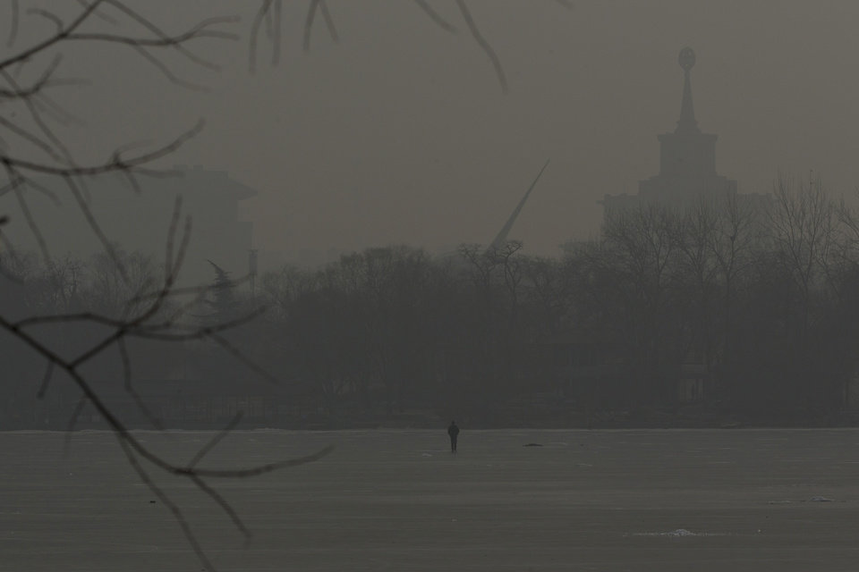 Photo - A man walks on an frozen lake on a hazy day in Beijing, China, Monday, Jan. 14, 2013. Beijing schools kept children indoors and hospitals saw a spike in respiratory cases Monday following a weekend of off-the charts pollution in China's smoggy capital, the worst since the government began being more open about air-quality data. (AP Photo/Alexander F. Yuan)