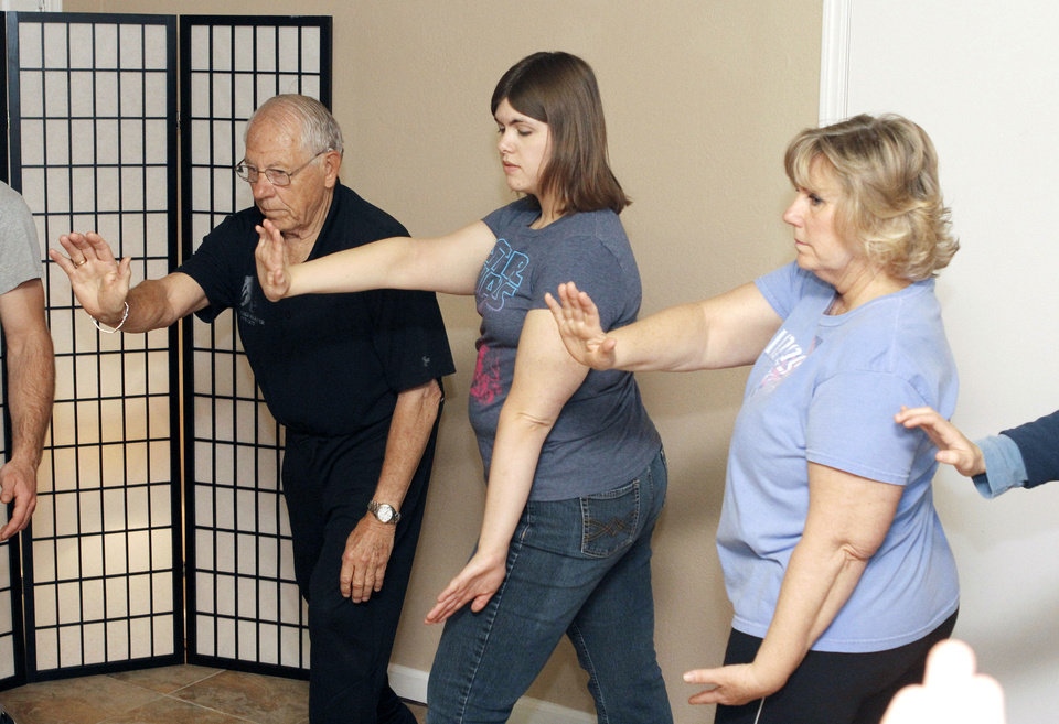Photo - boldDow McCarty, Shelly Roberson and Gretchen Schadegg practice some moves during a tai chi class for seniors at the Ntouch Medical Massage and Spa in Edmond taught by University of Central Oklahoma students.