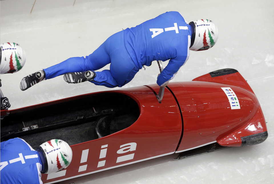Photo - The team from Italy ITA-1, piloted by Simone Bertazzo, start a run during the men's four-man bobsled training at the 2014 Winter Olympics, Wednesday, Feb. 19, 2014, in Krasnaya Polyana, Russia. (AP Photo/Michael Sohn)