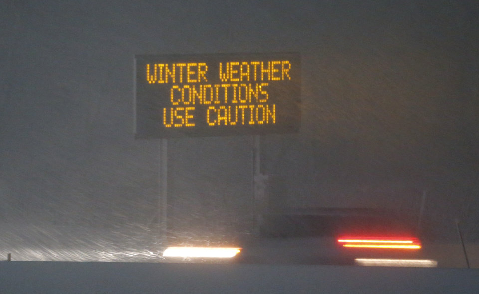 Photo - A vehicle travels past a warning sign on I-70 east of Topeka, Kan., Monday, Feb. 25, 2013.  Jayson Gosselin of the National Weather Service says parts of Colorado, Kansas and northern Missouri could get 10 to 12 inches of snow.  (AP Photo/Orlin Wagner)