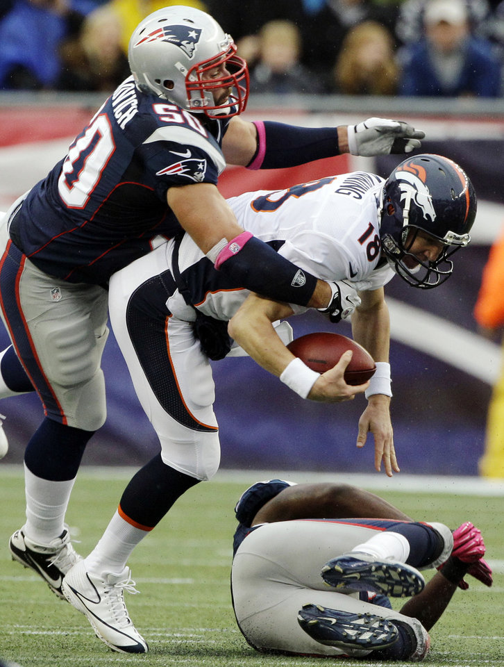 Denver Broncos quarterback Peyton Manning (18) is sacked by New England Patriots linebacker Jerod Mayo, bottom, as defensive end Rob Ninkovich wraps Manning up in the first quarter of an NFL football game, Sunday, Oct. 7, 2012, in Foxborough, Mass. (AP Photo/Stephan Savoia)