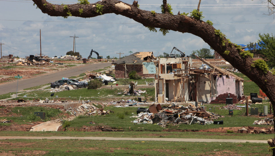 A tree in Veterans Memorial Park is shown in the foreground with damage from the EF5 tornado of May 20 behind it.  <strong>David McDaniel - The Oklahoman</strong>