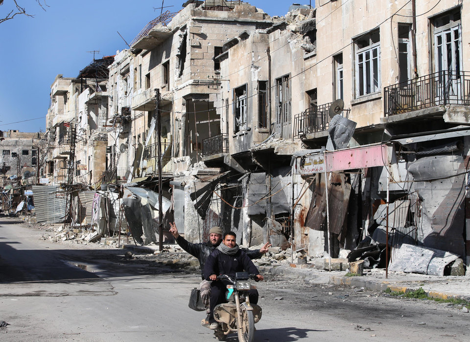 Photo - Syrians ride a scooter as one gestures,  as they pass by a destroyed street which was damaged by the shelling of the Syrian forces, at Maarat al-Nuaman town, in Idlib province, Syria, Tuesday Feb. 26, 2013. Syrian rebels battled government troops near a landmark 12th century mosque in the northern city of Aleppo on Tuesday, while fierce clashes raged around a police academy west of the city, activists said. (AP Photo/Hussein Malla)