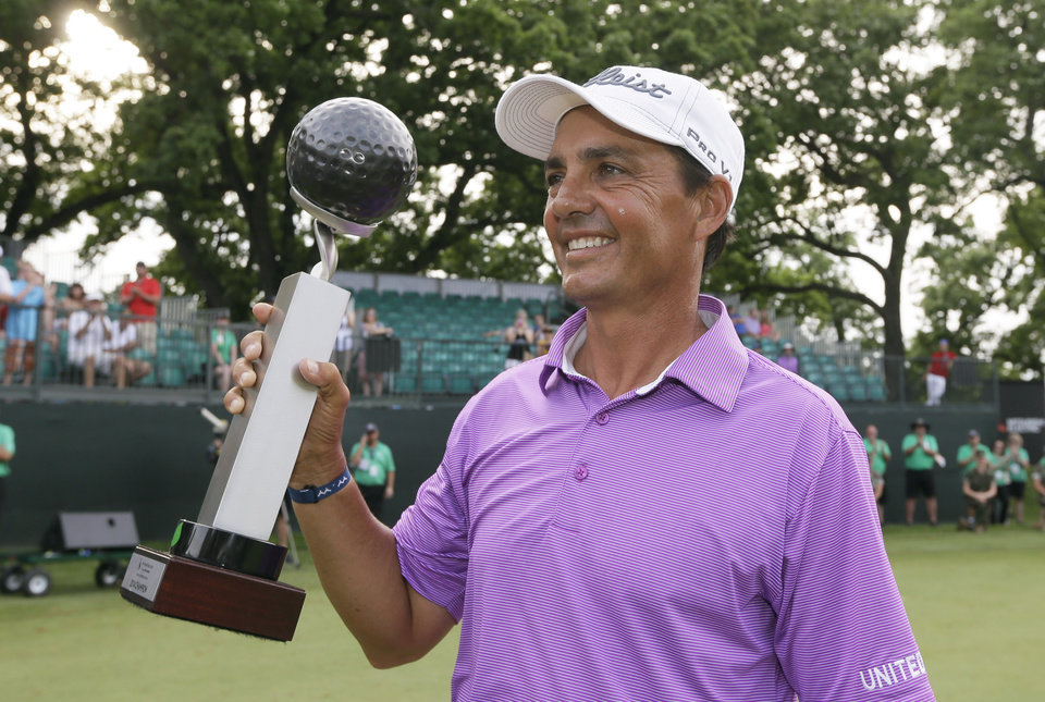 Photo - Tom Pernice Jr. holds the trophy after winning the Champions Tour's Principal Charity Classic golf tournament, Sunday, June 1, 2014, in Des Moines, Iowa. (AP Photo/Charlie Neibergall)