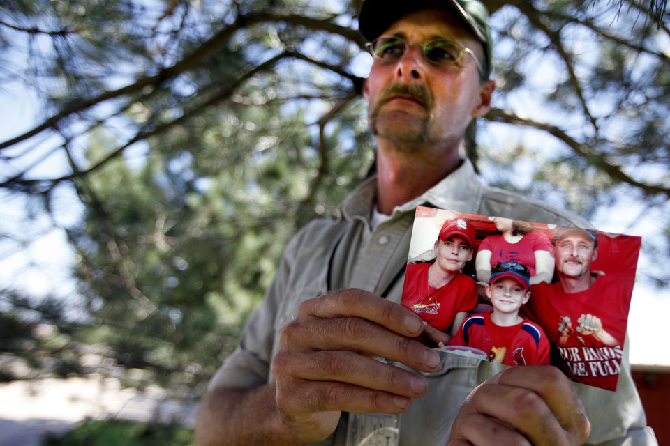 Photo - CHILD / CHILDREN / KIDS / SUICIDE / LAURA SMALLEY: Kirk Smalley holds a picture of himself, his 11-year-old stepson, Ty Field, and wife Laura at a St. Louis Cardinals game Thursday, June 17, 2010.  Photo by Miranda Grubbs, The Oklahoman ORG XMIT: KOD