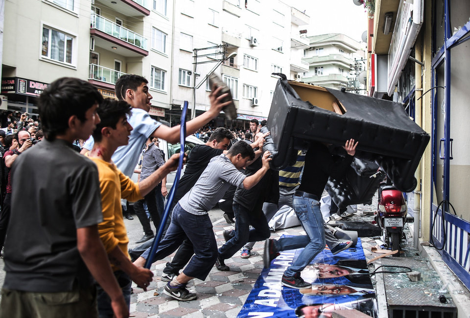 Photo - People attack the Soma offices of Prime Minister Recep Tayyip Erdogan's Justice and Development Party during his visit to the coal mine in Soma, Turkey, Wednesday, May 14, 2014. A violent protest erupted Wednesday in the Turkish city of Soma, where at least 238 coal miners have died after a mine explosion. Many in the crowd expressed anger at Prime Minister Recep Tayyip Erdogan's government. Rocks were being thrown and some people were shouting that Erdogan was a