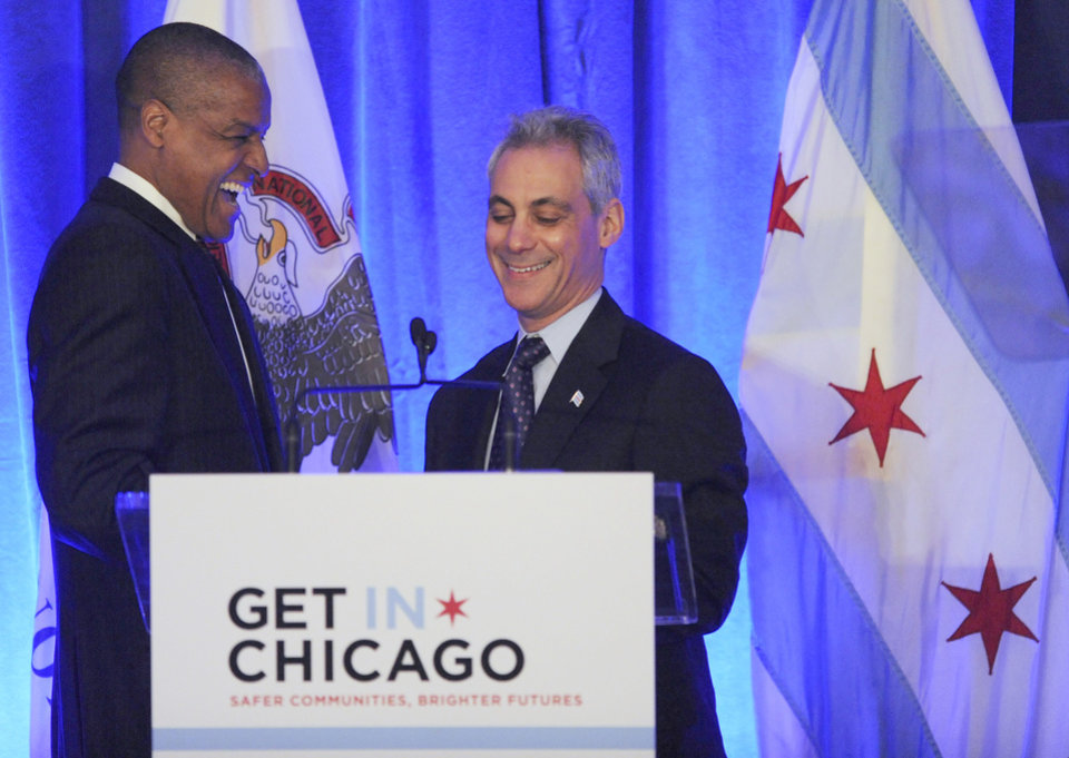 Photo - Chicago Mayor Rahm Emanuel, right, is introduced by Loop Capital Chairman and CEO James Reynolds Jr. left, during a luncheon at the Chicago Hilton in Chicago, Wednesday, April 10, 2013, before first lady Michelle Obama spoke. The first lady is visiting Chicago for a discussion with Emanuel and civic leaders on ways to combat youth violence. (AP Photo/Paul Beaty)