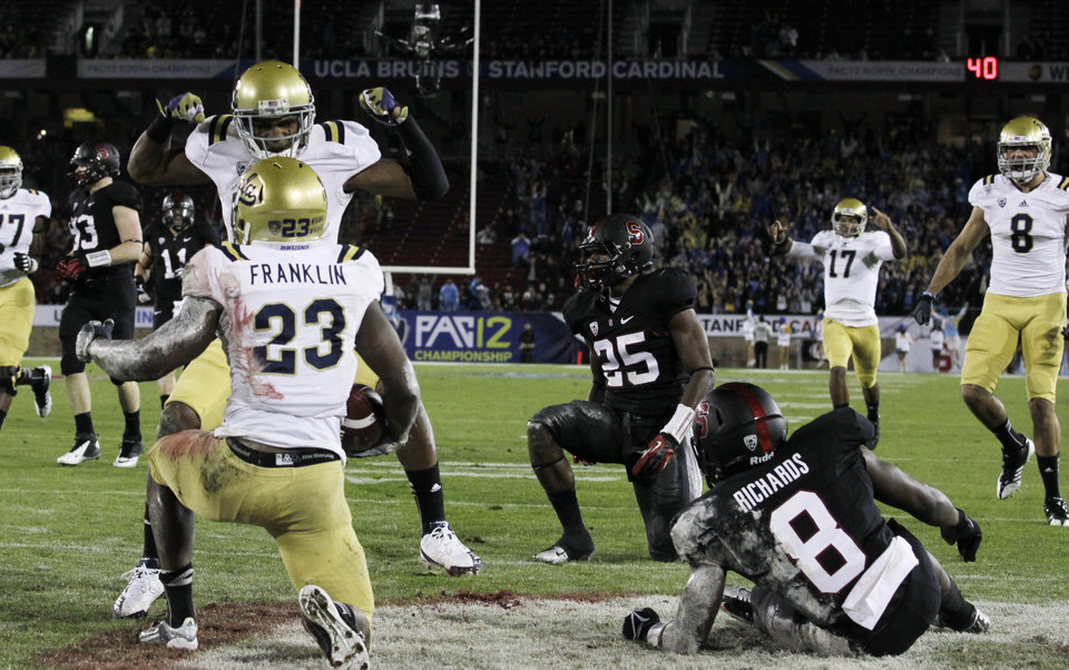 Photo - UCLA running back Johnathan Franklin (23) celebrates with teammates in the end zone after his 51-yard touchdown run against Stanford during the first half of the Pac-12 championship NCAA college football game in Stanford, Calif., Friday, Nov. 30, 2012. (AP Photo/Tony Avelar)