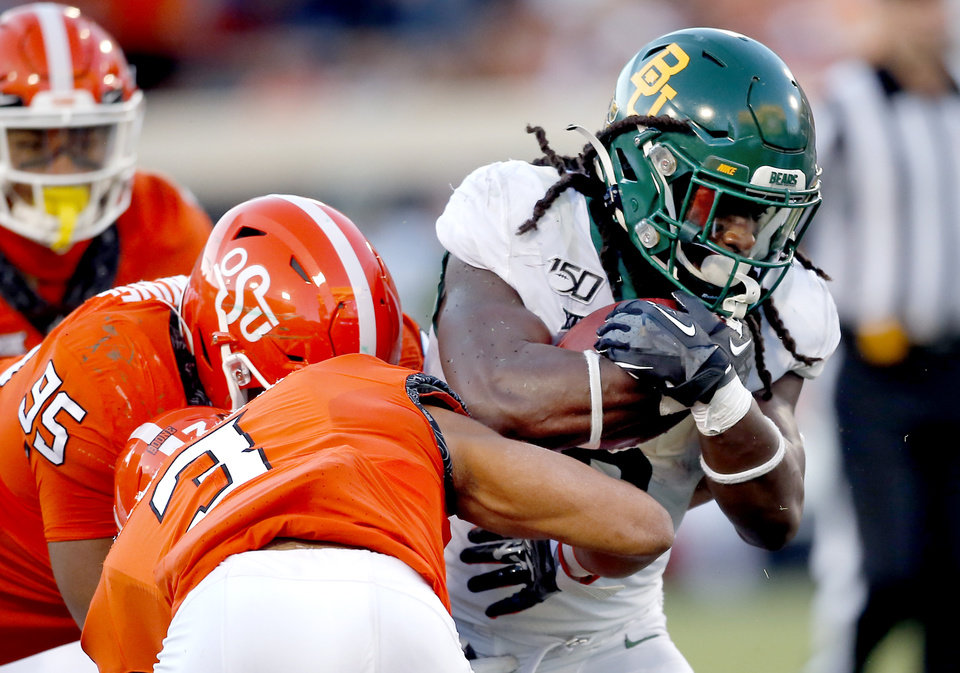 Photo - Oklahoma State's Israel Antwine (95) and Tre Sterling (3) tackle Baylor's JaMycal Hasty (6) in the fourth quarter during the college football game between Oklahoma State University and Baylor at Boone Pickens Stadium in Stillwater, Okla., Saturday, Oct. 19, 2019. Baylor won 45-27. [Sarah Phipps/The Oklahoman]