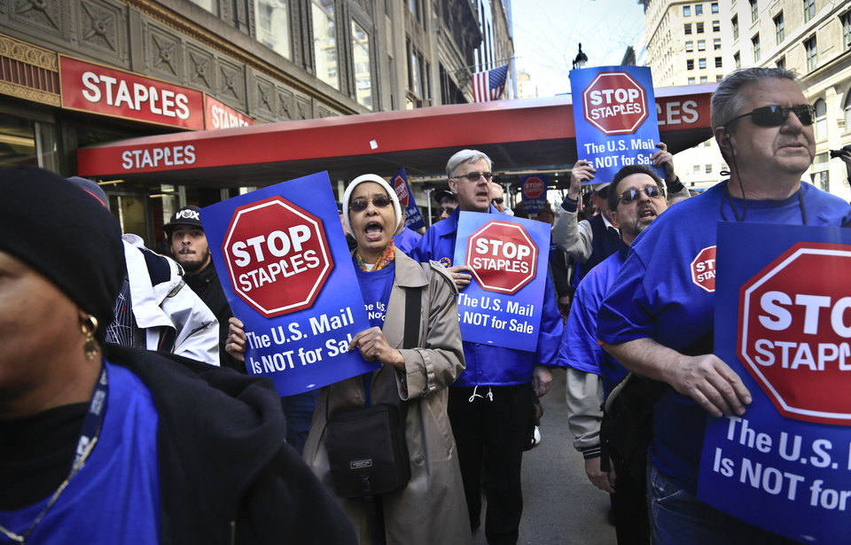 Photo - Post office workers march outside a Staples store chanting