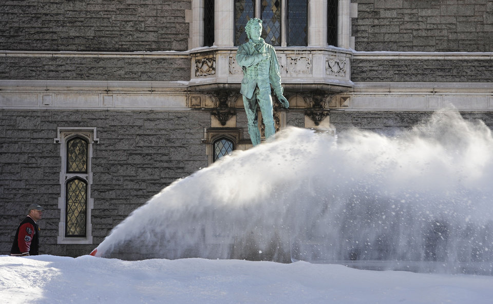 Photo - A man uses a snowblower around a statue of Nathan Hale outside the Wadsworth Atheneum after a winter storm in Hartford, Conn., Sunday, Feb. 10, 2013. A howling storm across the Northeast left much of the New York-to-Boston corridor covered with more than three feet of snow on Friday into Saturday morning. (AP Photo/Jessica Hill)