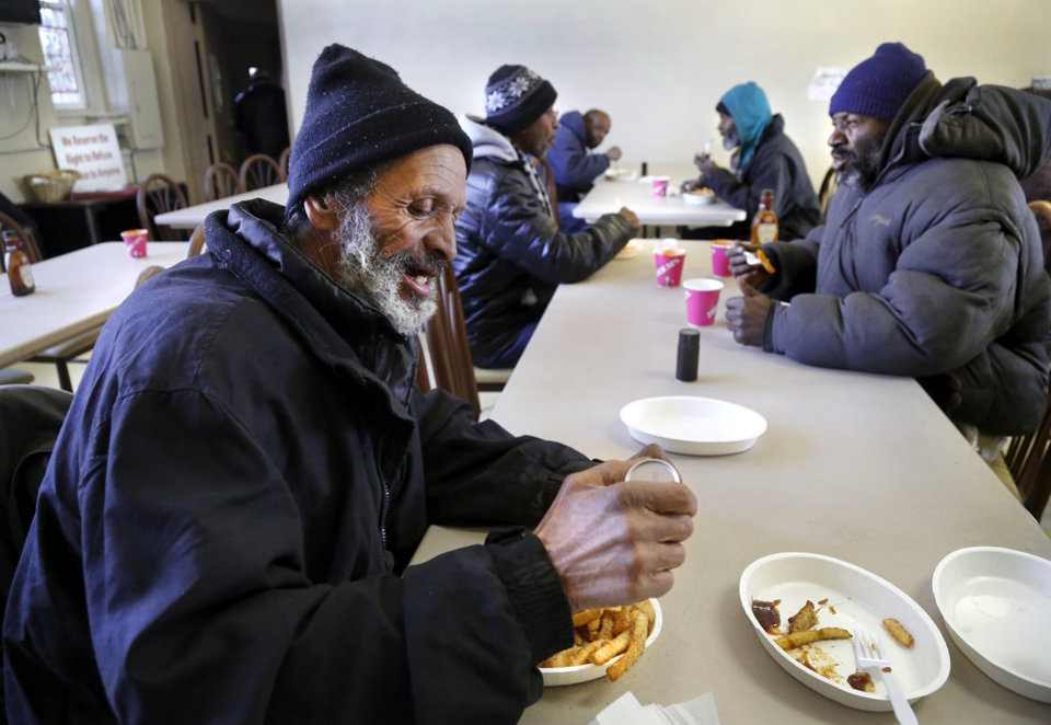 Photo - Gary Duncan, left, adds salt to his French fries as he eats a hot meal with other homeless men in the dining hall at the Jesus House as they deal with frigid sub-freezing temperatures, part of a major winter storm that continues to grip much of the central sections and the eastern half of the United States. Photo taken Monday, Jan. 6, 2014.  Photo by Jim Beckel, The Oklahoman