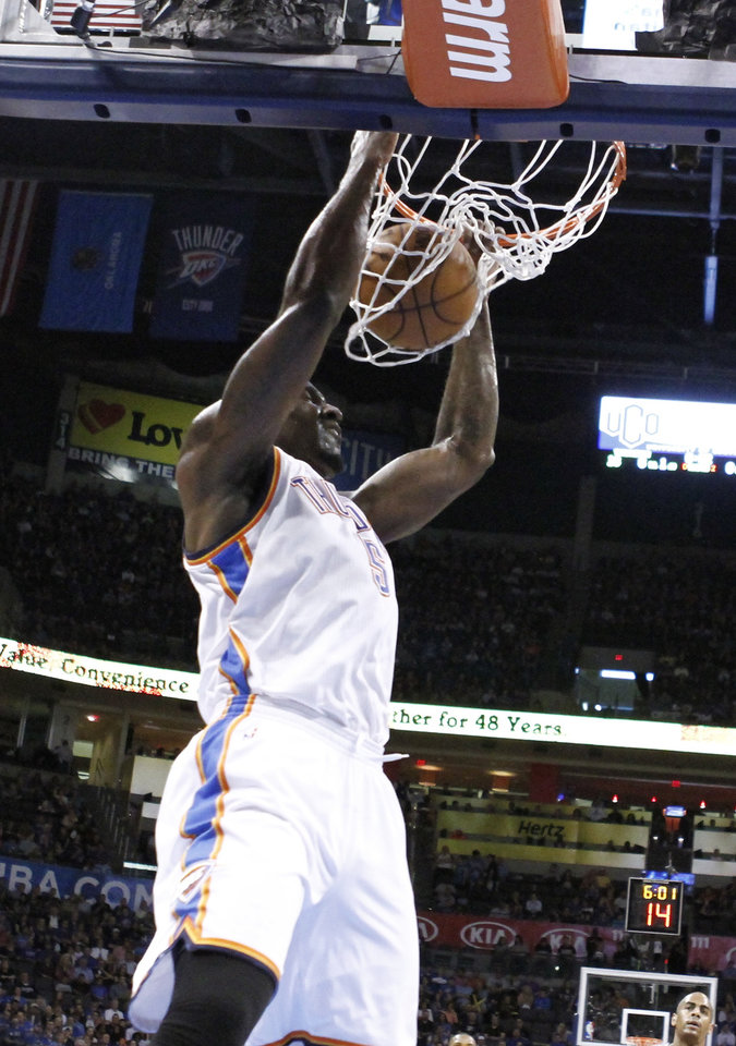 Photo - Oklahoma City Thunder center Kendrick Perkins dunks against the Orlando Magic during the first quarter of an NBA basketball game in Oklahoma City, Friday, March 15, 2013. Oklahoma City won 117-104. (AP Photo/Alonzo Adams)