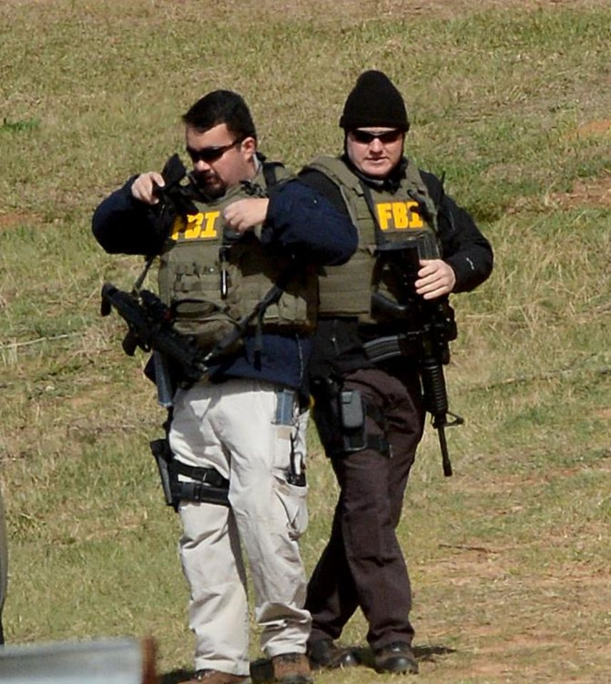 Photo - Law enforcement officials continue to work the scene of an ongoing hostage crisis in Midland City, Ala., Friday, Feb. 1, 2013. Local, state and federal officers wait out a man accused of shooting and killing a school bus driver, then snatching a 5-year-old child. Suspect Jimmy Lee Dykes has been holed up in a bunker on his property with the child since the late afternoon shooting on Tuesday, Jan. 29, 2013. (AP Photo/al.com, Julie Bennett)