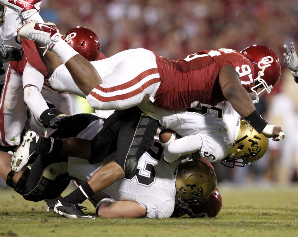 Photo - OU's Jamarkus McFarland brings down Colorado's Rodney Stewart during the college football game between the University of Oklahoma (OU) Sooners and the University of Colorado Buffaloes at Gaylord Family-Oklahoma Memorial Stadium in Norman, Okla., Saturday, October 30, 2010. Photo by Bryan Terry, The Oklahoman