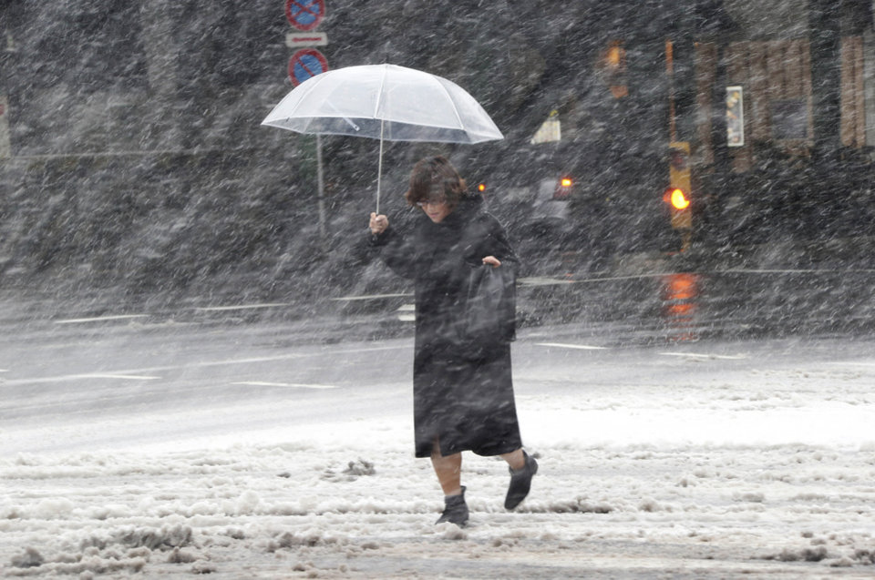 Photo - A woman walks against blowing snow in Tokyo, Saturday, Feb. 8, 2014. The Japan Meteorological Agency issued the first heavy snowfall warning for central Tokyo in 13 years. (AP Photo/Koji Sasahara)