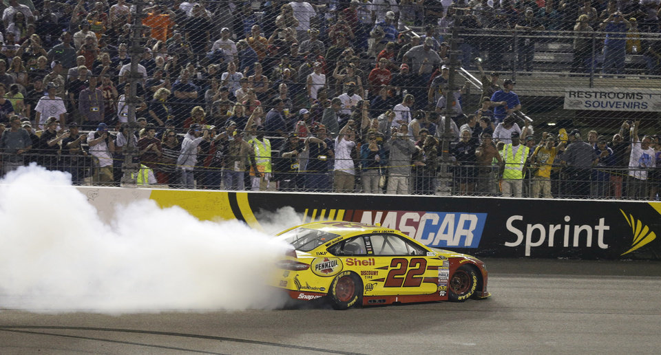 Photo - Joey Logano does a burnout following his win in the NASCAR Sprint Cup auto race at Richmond International Raceway in Richmond, Va., Saturday, April 26, 2014. (AP Photo/Steve Helber)