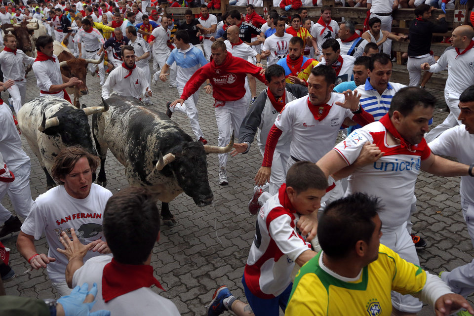 Photo - Revelers run with fighting bulls during the running of the bulls of the San Fermin festival, in Pamplona, Spain, Monday, July 7, 2014. Revelers from around the world arrive in Pamplona every year to take part on some of the eight days of the running of the bulls glorified by Ernest Hemingway's 1926 novel