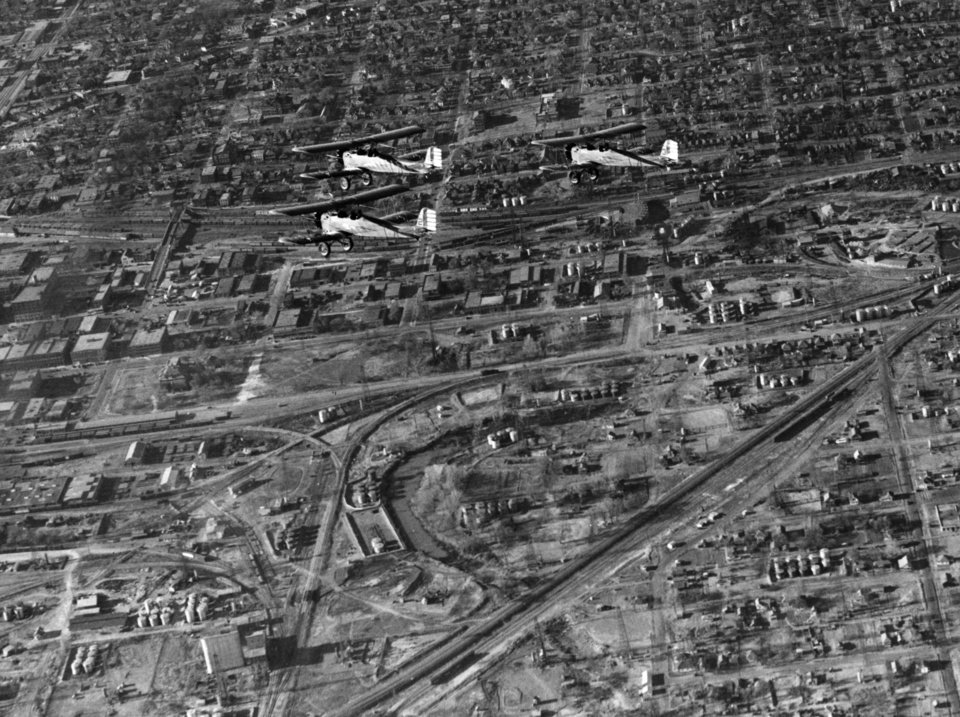 OKLAHOMA CITY / SKY LINE / OKLAHOMA / AERIAL VIEWS / AERIAL PHOTOGRAPHY / AIR VIEWS: SO HIGH - Oklahoma City saw Army day celebrated both on the ground and in the air Monday. While crowds were gathered around exhibits in Civic Center park on the east side of North Broadway, three planes from the army air reserve base at the the municipal airport, flying in formation, glided through tricky maneuvers overhead. Piloting the army planes were Maj. Clint Johnson,lead; Capt. Bill Bleakley, left, and First Lieut. John Cook, right. The picture by C.J. Kaho, staff photographer, was taken from a plane piloted by Hardy Young. Staff photo by C.J. Kaho. Photo dated 04/06/1936 and published 04/07/1936 in The Daily Oklahoman.