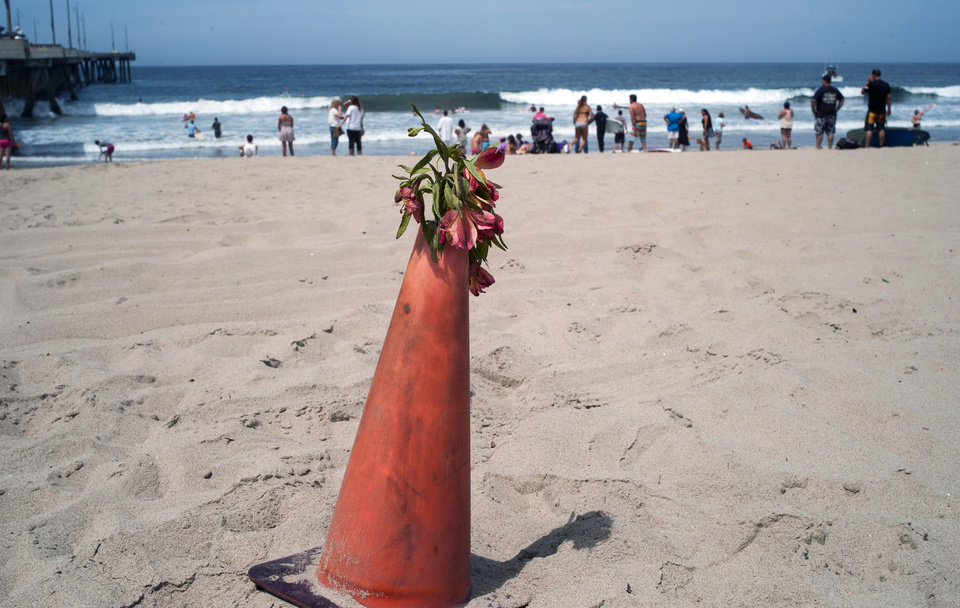 Photo - A bouquet of flowers is set on a warning cone at the Venice Beach pier in Los Angeles, Monday, July 28, 2014. Los Angeles' popular Venice Beach teemed with people enjoying a weekend outing on the boardwalk and sand when lifeguards and other witnesses say lightning from a rare summer thunderstorm hit without warning, injuring or rattling more than a dozen people and leaving a 21-year-old man dead. The witnesses said the strike hit with a tremendous boom about 2:30 p.m. Sunday, July 27, rattling buildings and showering a lifeguard headquarters with sparks. (AP Photo/Damian Dovarganes)