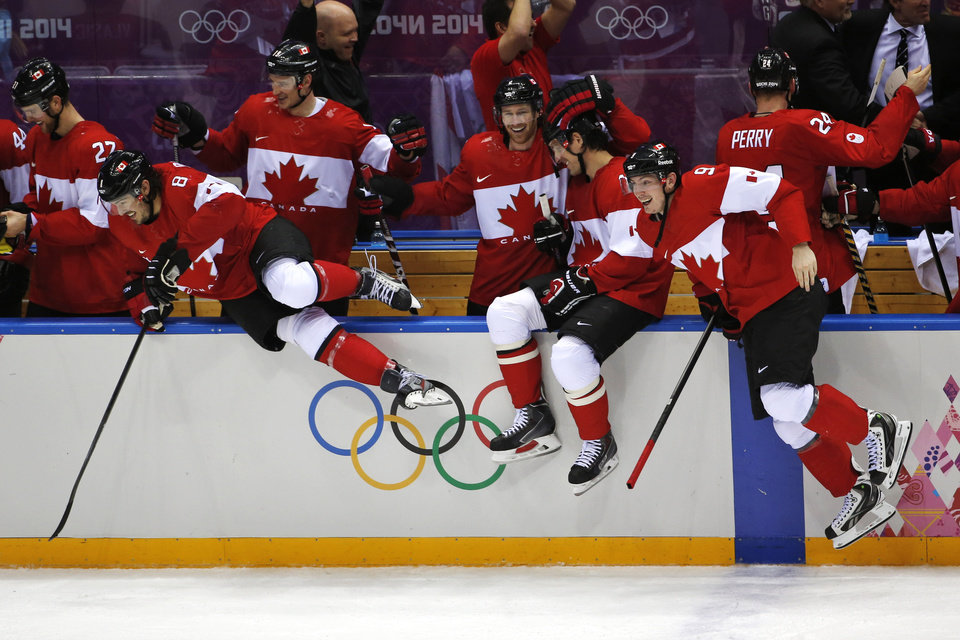 Photo - The Canadian bench jumps out of the bench area to celebrate their 3-0 win over Sweden in the men's gold medal ice hockey game at the 2014 Winter Olympics, Sunday, Feb. 23, 2014, in Sochi, Russia. (AP Photo/Petr David Josek)