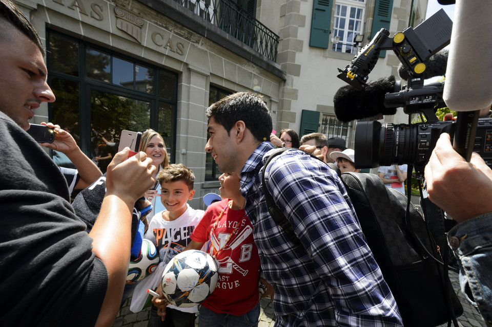 Photo - Uruguay's soccer player Luis Suarez poses with fans as he leaves the international Court of Arbitration for Sport, CAS, surrounded by fans and media after a five hour hearing in Lausanne, Switzerland, Friday, Aug. 8, 2014. Suarez appealed to the CAS against the four-month ban imposed by FIFA on the Uruguay striker. Suarez was banned for biting Italy's Giorgio Chiellini at the FIFA Brazil 2014 World Cup. (AP Photo/Keystone, Laurent Gillieron)
