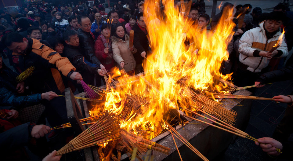 Temple goers gather to burn incense as they offer prayers on the first day of Chinese Lunar New Year at Yonghegong Lama Temple in Beijing, Sunday, Feb. 10, 2013. Millions across China are celebrating the arrival of the Lunar New Year, the Year of the Snake, marked with a week-long Spring Festival holiday. (AP Photo/Andy Wong)