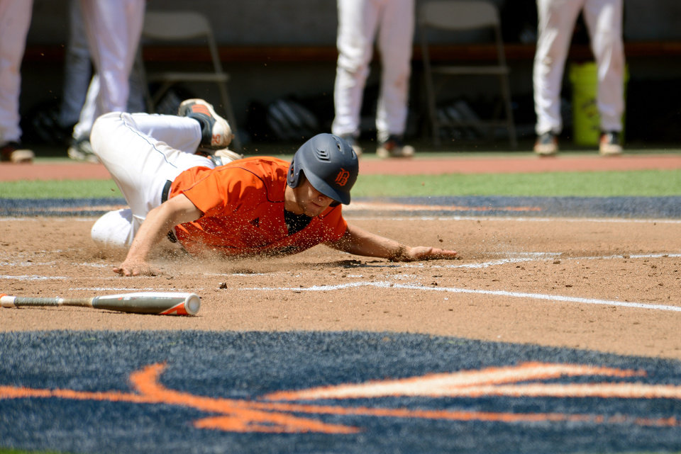 Photo - Bucknell's Jon Mayer scores on a hit by teammate Rob Krentzman during the first inning of an NCAA college baseball regional tournament game against Liberty in Charlottesville, Va., Saturday, May 31, 2014. (AP Photo/Pat Jarrett)